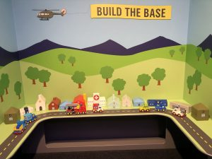 "Photo of a miniature army base with small buildings lined alongside a road with plastic cars. In the background is a cartoon scene of trees, grass, and mountains with a helicopter flying above trailing a banner that says ""build a base."""