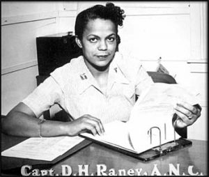 Black and white photograph of Della Raney in a captain's uniform, sitting at a desk, flipping through paper charts.