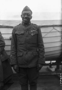 Black and white photo of an African American Soldier in uniform on the deck of a ship in front of a life boat.