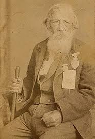 Sepia tone photograph of an elderly Jordan Noble sitting down and wearing multiple medals on his breast pocket