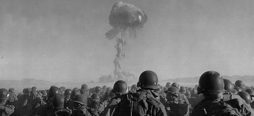 A group of Soldiers look on at a mushroom cloud from a nuclear bomb test.
