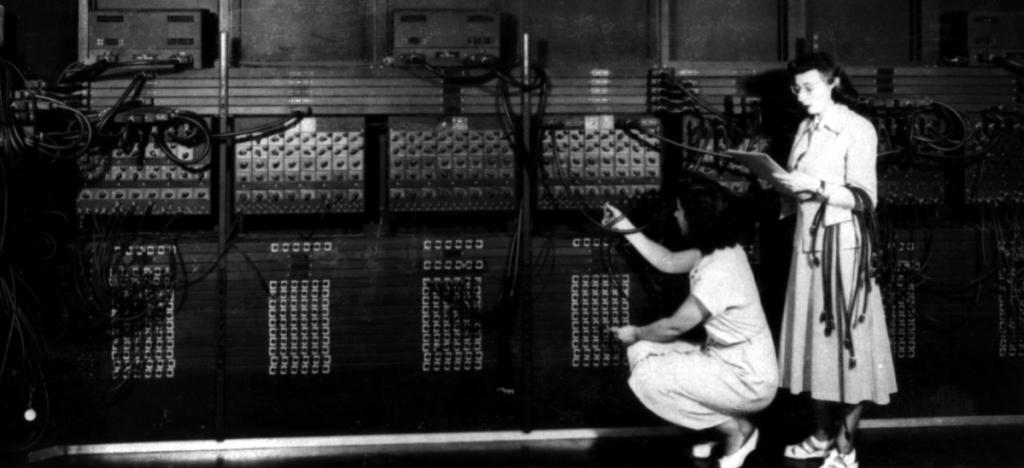 Two women rewire a computer that takes up an entire wall