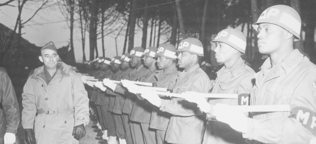 White officer inspects a line of Black military police