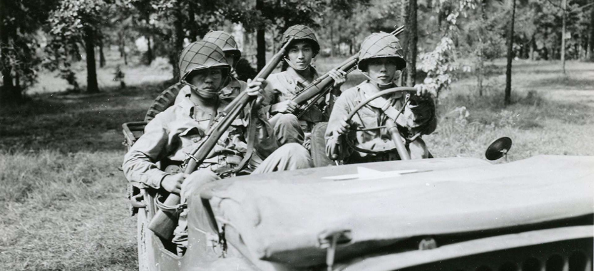 4 Japanese American Soldiers with weapons sitting in a jeep